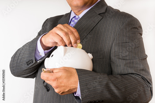 Businessman holding a piggybank and saving change