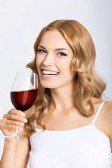 Young happy woman with glass of redwine, on gray