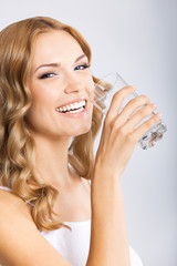 Young woman drinking water, on gray