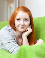 red haired young girl relaxing on couch