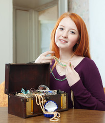 red-headed girl looks jewelry