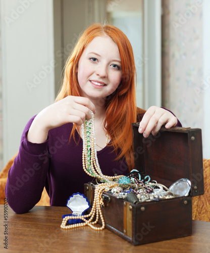 red-headed girl looks jewelry in treasure chest