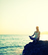 woman meditating in  lotus yoga on beach