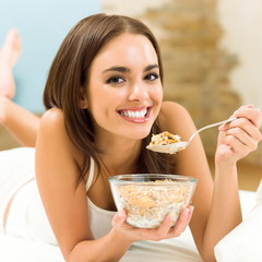 Young woman eating cereal muslin, flakes