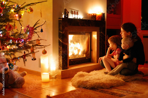 Young mother and her daughters by a fireplace