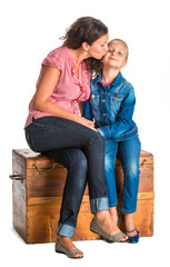 Mother and daughter sitting on a wooden chest