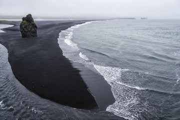 Black volcanic sand on the south coast of Iceland in rainy weath