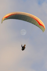 A paraglider flying in the sunset