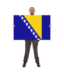 Smiling businessman holding a big card, flag of Bosnia and Herze