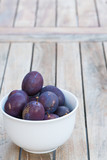Arrangement of damson plums on wooden boards