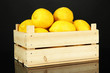 Ripe lemons in wooden box isolated on black