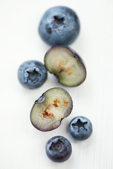 Whole and halved blueberries on white wooden background