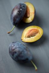 Freshly harvested organic plums, vertical shot
