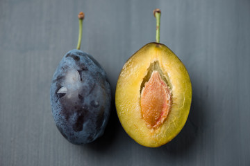 Whole and halved plums on wooden background, view from above