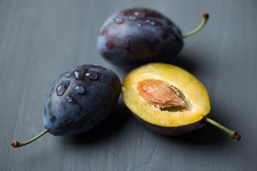 Fresh plums, grey wooden background, horizontal shot