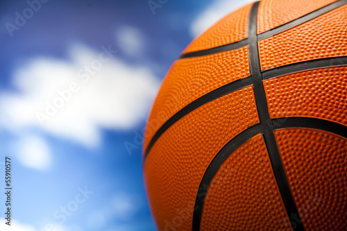 Basketball ball over blue sky background
