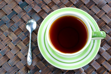 Cup of tea with spoon on bamboo wease background .