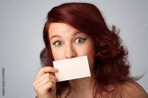 Cute girl holding white card at front of her lips with copy spac