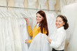 happy women chooses bridal clothes at wedding store.