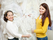 woman helps the bride in choosing bridal clothes