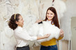 women chooses bridal outfit at wedding store