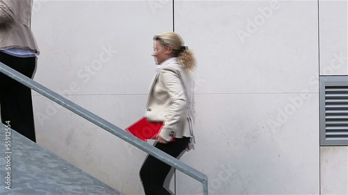 Two business women running up stairs
