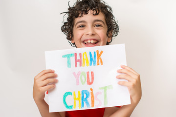 Hispanic child holding a religious sign