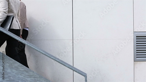 Businesswomen talking while walking up staircase