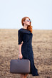 Redhead girl with suitcase at autumn field