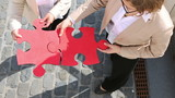 Business women holding jigsaw puzzle pieces