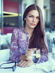 Brunette beauty drinking water in restaurant
