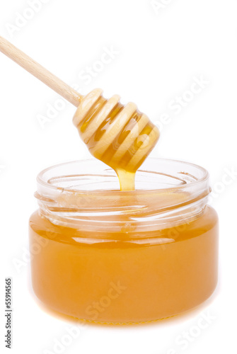 Honey dripping into a jar with a special spoon.