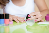 Woman painting fingernails at home