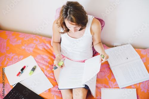 Woman studying on bed in the comfort of her home