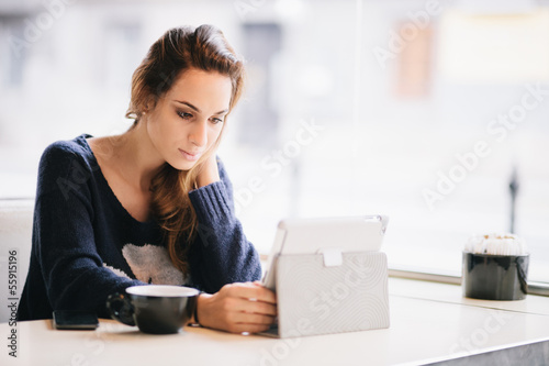 Young woman / student using tablet computer in cafe