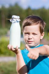 Мальчик с бутылкой молока в руке показывает большой палец вверх