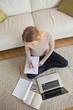 Blonde doing homework and sitting on floor using laptop