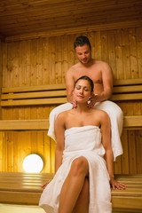 Man giving his girlfriend a neck massage in sauna