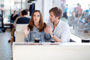 Young couple arguing in a cafe. She's had enough, boyfriend is a