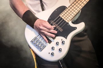 musician playing a bass guitar on stage