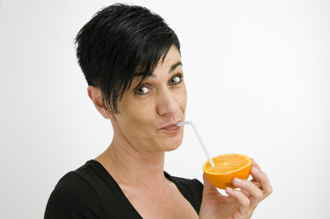 woman with drinking straw and orange