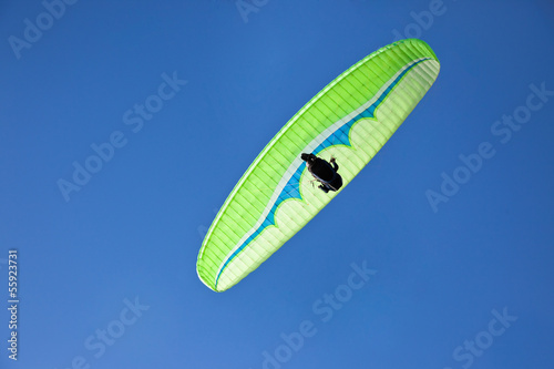 Green paraglider flying in blue sky.