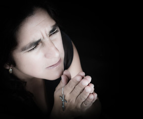 Emotional portrait of a latin woman praying isolated on black