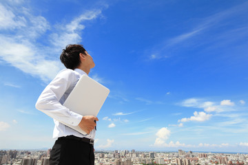 business man using laptop and look to blue sky
