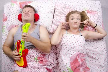 Пара в постели: муж играет на гитаре, жена заткнула пальцами уши