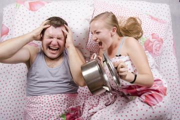 Жена будит мужа ударом крышки о кастрюлю