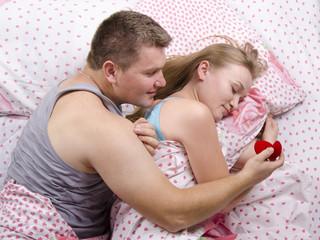 Парень готовится подарить кольцо девушке лежа в кровати