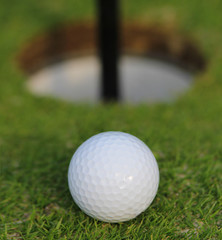 Golf ball about to fall into the cup, on green grass. Closeup