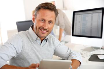 Salesman in office using digital tablet