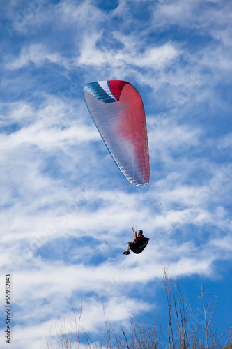 Paraglider flying in cloudy sky.